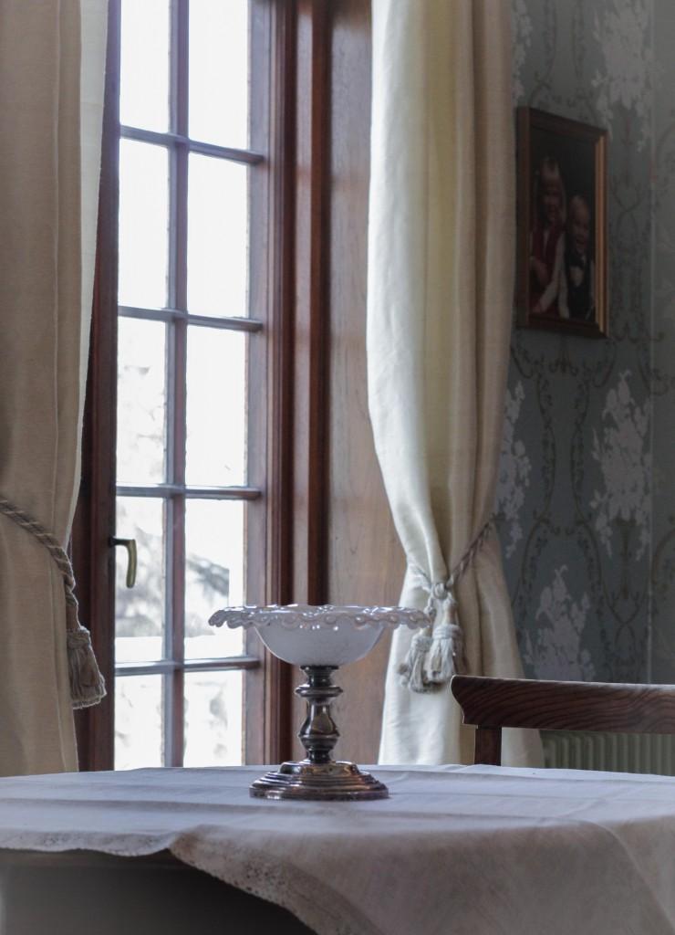 Lekre gardiner er sydd i silke fargen på stoffet går igjen i detaljer på tapeten.
