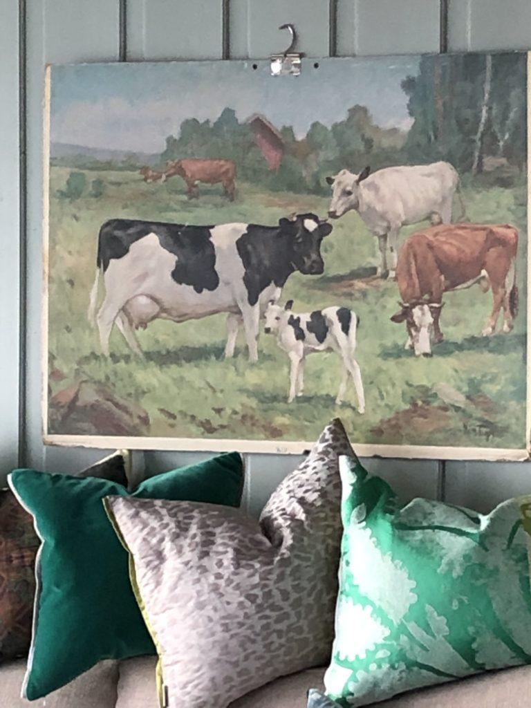 Skoleplakaten med kuene gir stuen glede og humor. Om sommeren beiter kuene på utsiden av huset.